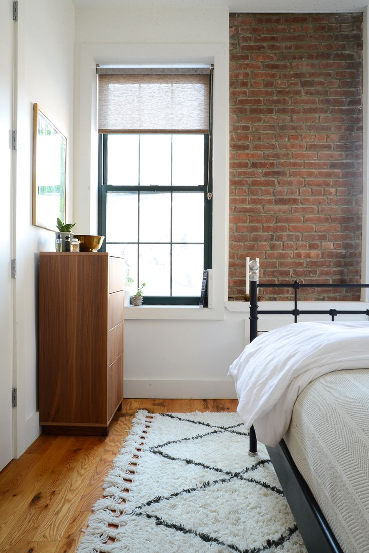 love the combo of the wood floor rug exposed brick and black window trim - Brick Apartment 2015