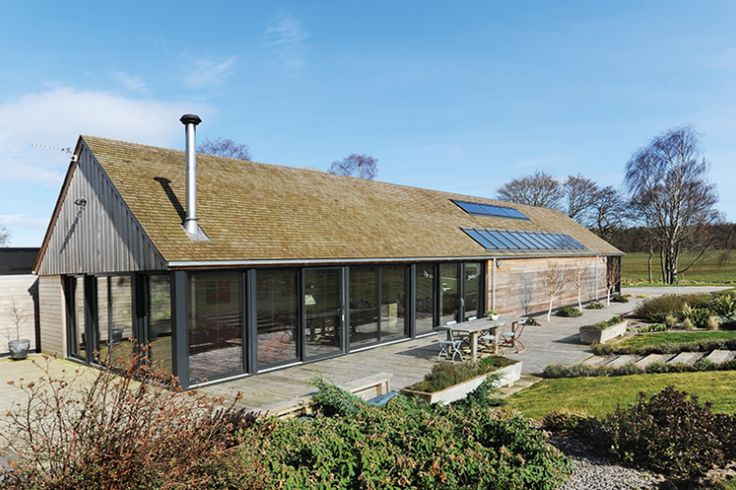 The house features extensive glazing, cedar cladding and cedar roof tiles. Like this but smaller and with round roof