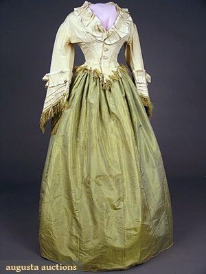 "Silk dress, c1870; Two-piece, silk taffeta chartreuse skirt lined with brown cotton, jacket cream silk faille trimmed in cream satin and chartreuse silk fringe, fabric covered buttons, Sh-Sh 16.5"", B 35"", W 24"", Skirt L 45"""