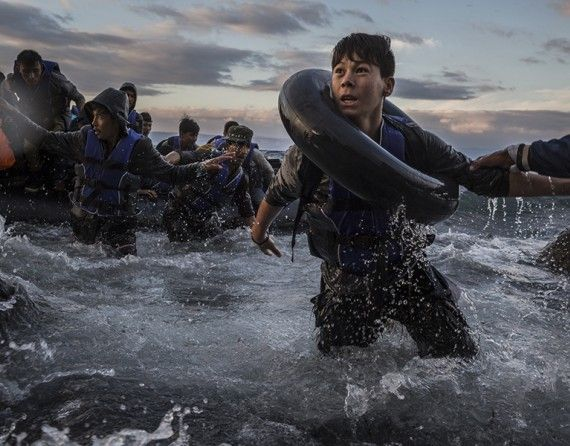 After battling rough seas and high winds from Turkey, refugees arrive by rubber raft on a jagged shoreline of Lesbos. Fearing capsize or puncture, some panicked and jumped into the cold water in desperation to reach land (The New York Times/Tyler Hicks - October 1, 2015).