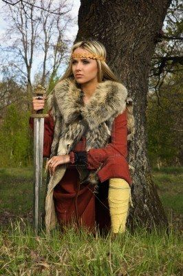 Portrait of the blonde girl in the Scandinavian suit with sword