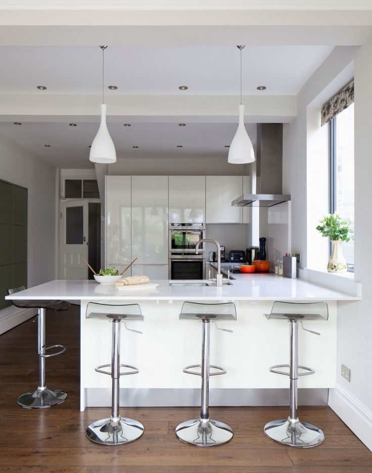Modern white kitchen with hi gloss units and breakfast bar for Salle a manger quartz