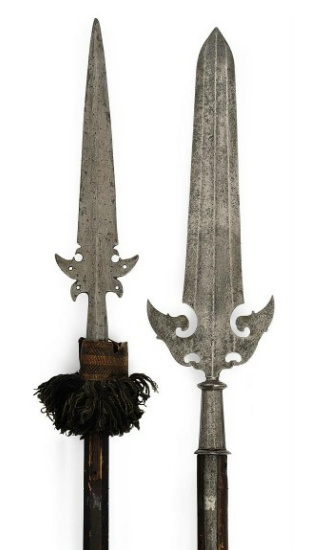 TWO PARTIZANS, PROBABLY ITALIAN   EARLY 17TH CENTURY   The first with broad triangular blade, each side with three medial ridges forming two shallow full length fullers, the lower part with two elaborately shaped pierced side-lugs, moulded tapering faceted socket, and short side-straps, on wooden haft of circular section; the second with tapering with swelled tip and medial ridge on each side, the lower part with pierced beak-shaped side-lugs, and tapering socket