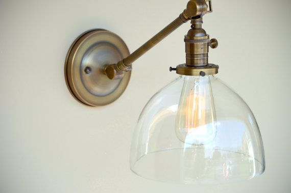 Sconce Lighting with Clear Glass Dome Shade Adjustable Arm Fixture Here is a beautiful wall sconce with an 8 clear glass dome shade that can be adjusted easily with the 2 strong hinged joints. These glass shades match great with my pendant lighting which you can purchase in the same style. This wall sconce is pictured with an antique style edison bulb and is available for sale in my shop. All my lighting comes with all the mounting hardware necessary to be easily installed This fixture…