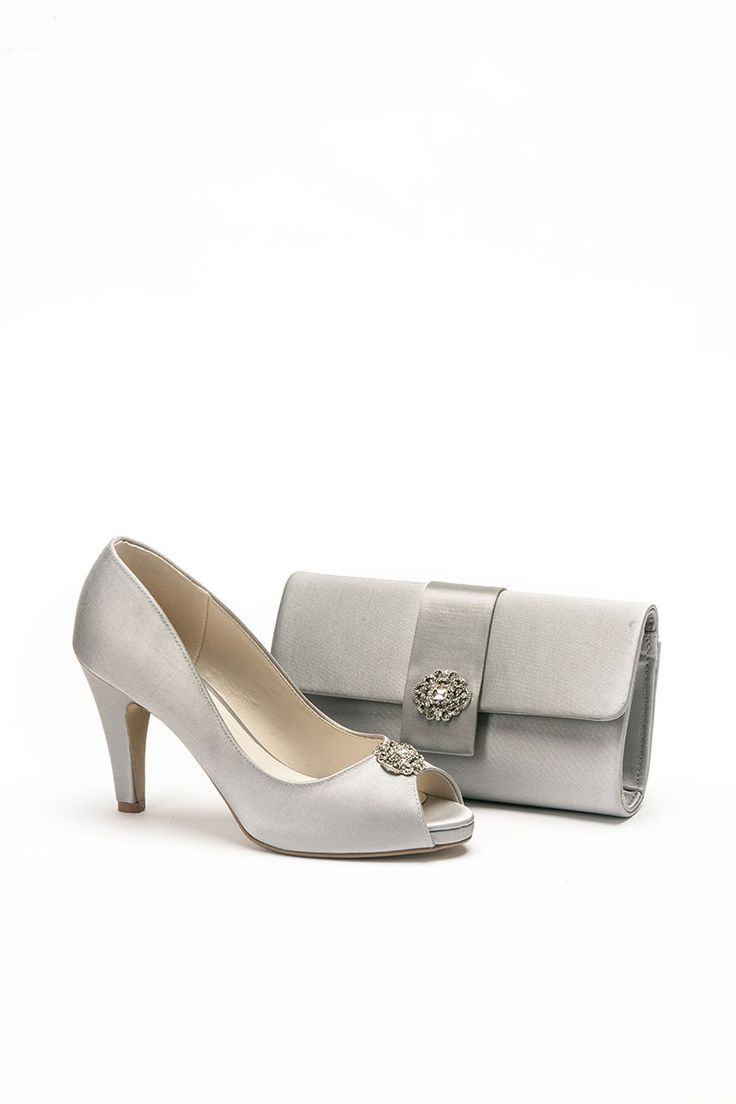 Mid height silver shoe with silver brooch to front and matching bag. Product code – P11 Colour – Silver