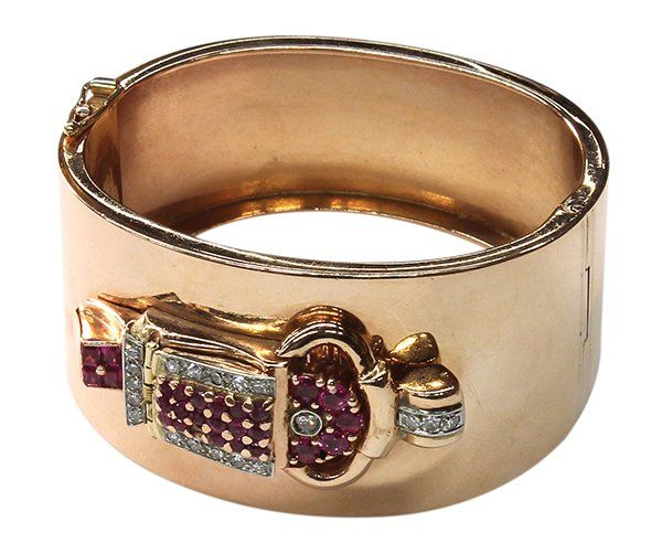 A Retro Era rose gold, diamond and ruby covered watch bangle  The hinged watch cover is decorated with diamonds, estimated total weight 0.32 carats; rubies estimated total weight 1.92 carats; seventeen jewel manual wind movement; width: 31.38 to 22.94 mm.