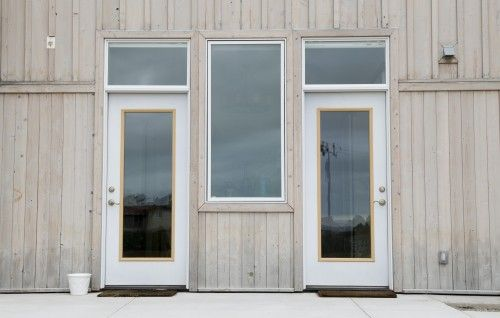 exterior with whitewashed wood paneling and white metal doors
