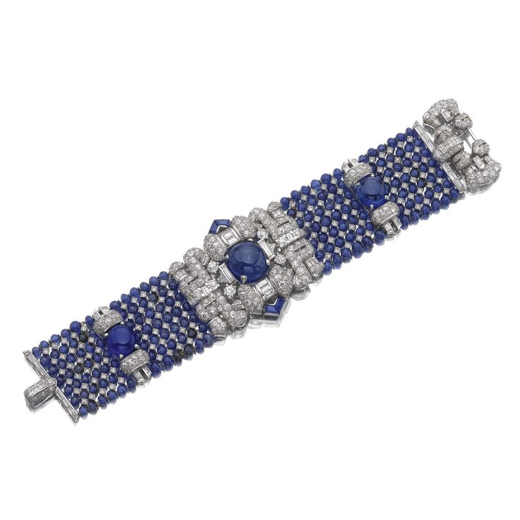 The central panel highlighted with a round cabochon sapphire set within a surround of baguette and circular-cut diamonds and calibré-cut sapphires, continuing to a mesh of sapphire beads and single-cut stones, accented with arched diamond set motifs and two cabochon sapphires