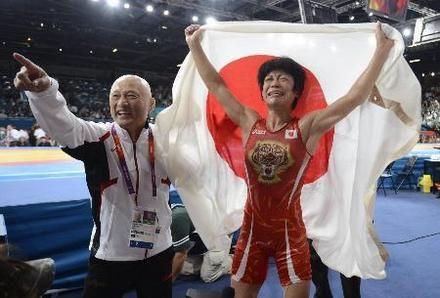 女子48キロ級で金メダルを獲得し、日の丸を掲げて大喜びの小原日登美。左は栄和人監督=エクセル(共同)