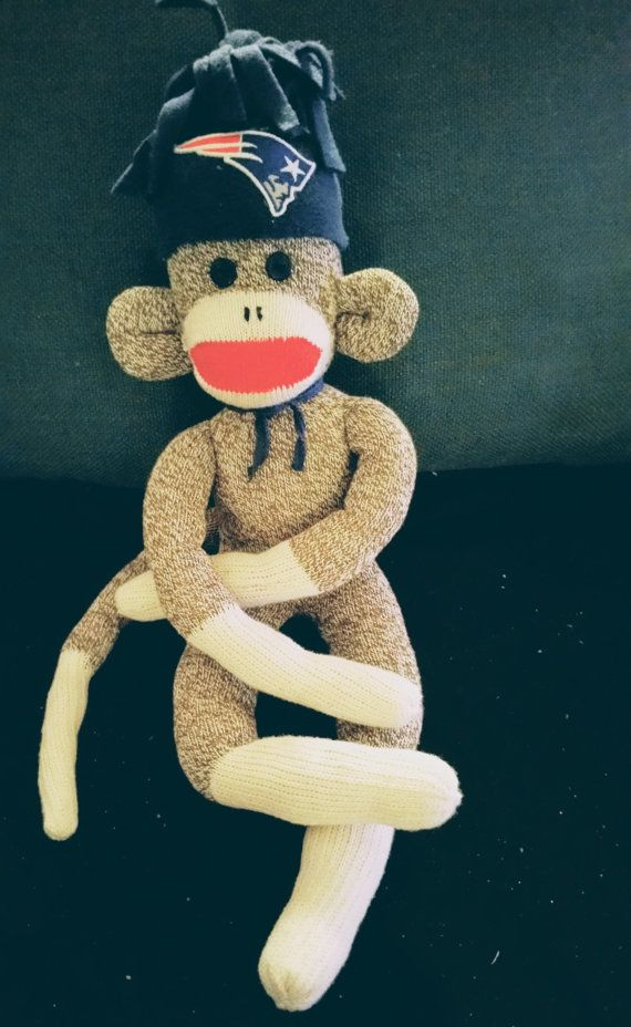 Support our latest Super Bowl winners with our New England Patriots sock monkey. This adorable stuffed toy wears a jaunty hat adorned with the Patriots' team logo. Show your love for Tom Brady and the rest of the team with this handcrafted toy!  Surprise your favorite Pats fan with this unique handmade gift. Little NFL fans, as well as grown-ups, will love this football-themed toy. Whether buying for yourself or giving as a gift, this cute sock monkey is a must-have for any New England…