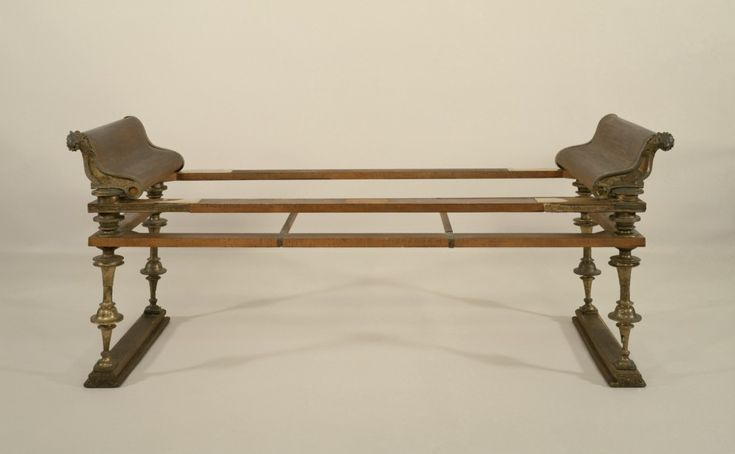 On this example, bronze fittings decorate a wood frame (restored). Straps originally would have supported a mattress covered with luxurious textiles. The ends of the couch are decorated with bronze fulcra, the curving ends of the armrests, which terminate in lion heads in the front and duck heads in the back.