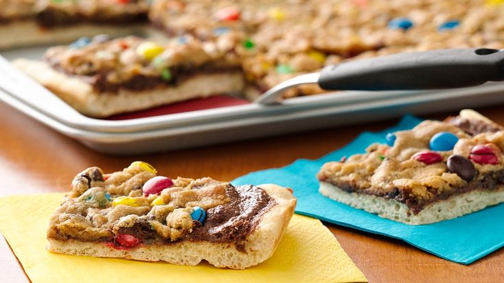 Cookies and candy pair as toppings for this kid-friendly dessert pizza! Have the kids help with the pizza making--little hands are perfect for crumbling the cookie dough and adding the candy.