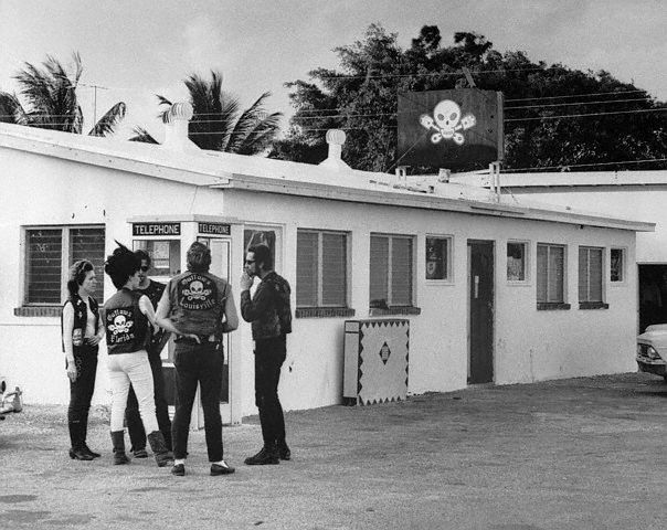 """11/26/1967-West Palm Beach, FL- Case involving members of """"Outlaws"""" motorcycle club, who are accused of nailing a female member of their club to a tree for holding out $10. Photo shows a group of """"Outlaws"""" outside """"Kitty's"""" after it was closed"""