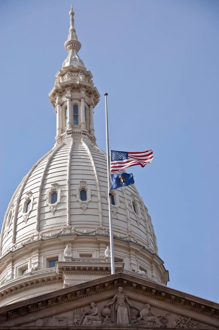 Photo of U.S. and Michigan flags at half-staff atop the Michigan State Capitol.