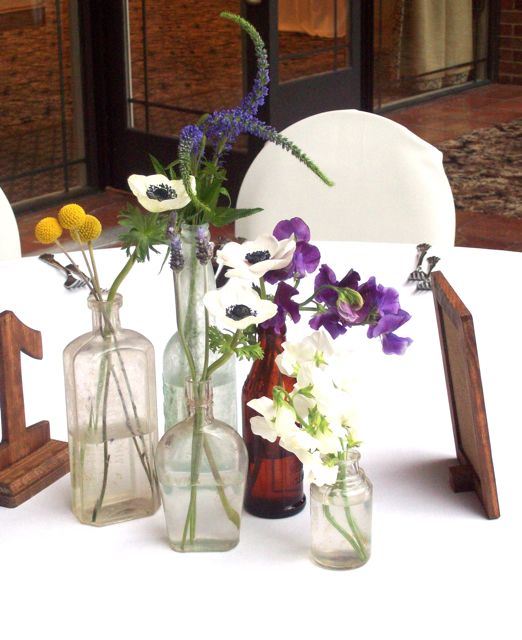Vintage bottle centerpieces with anemone, sweet pea, and craspedia.  Anthropology table number.