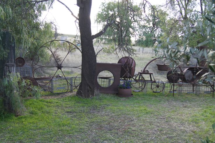 Awesome found objects dividing fence my Master made!  For scale, the large wheel is about 1.5m (5 ft) high.