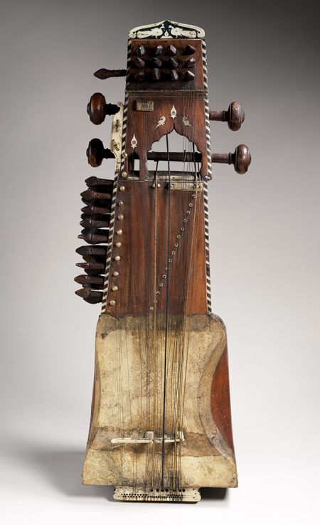Sarangi, ca. 1900, India, 75cm. The most important bowed instrument of classical Hindustani music of Northern India and Pakistan. A rigid horsehair bow (not shown) rhythmically sounds the gut melody strings, which cross over an ivory elephant-shaped bridge (bara ghurac). Melody and virtuosic embellishment are produced by pulling the strings to the side with the fingernails.