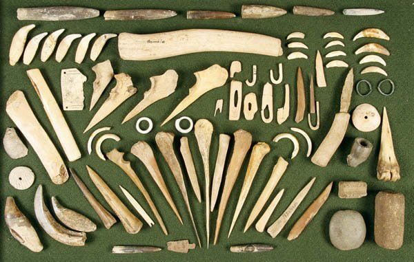 NATIVE AMERICAN INDIAN BONE AND ORGANIC ARTIFACTS AND MORE a group of well over 75 various items, the majority bone tools such as awls, punches, spatula, perforators, hooks, pins (greatest length 9.5 inches) together with other artifacts, 3 shell pendants, copper rings, shell ornaments, bear and elk teeth, relic metal trade point, pipe bowl fragment and some stone tools. Mostly circa 1750-1850, some items earlier.