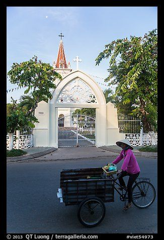 Woman bicycling in front of church. Tra Vinh, Vietnam
