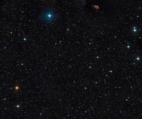 На этом широкоугольном снимке -  область неба вокруг молодой кратной системы GG Tauri, расположенной в самом центре изображения. На снимке также можно видеть пылевое облако и свидетельства звездообразования в его верхней части. Как и GG Tau, это часть комплекса Темного облака в Тельце (Taurus Dark Cloud). / Astro Analytics