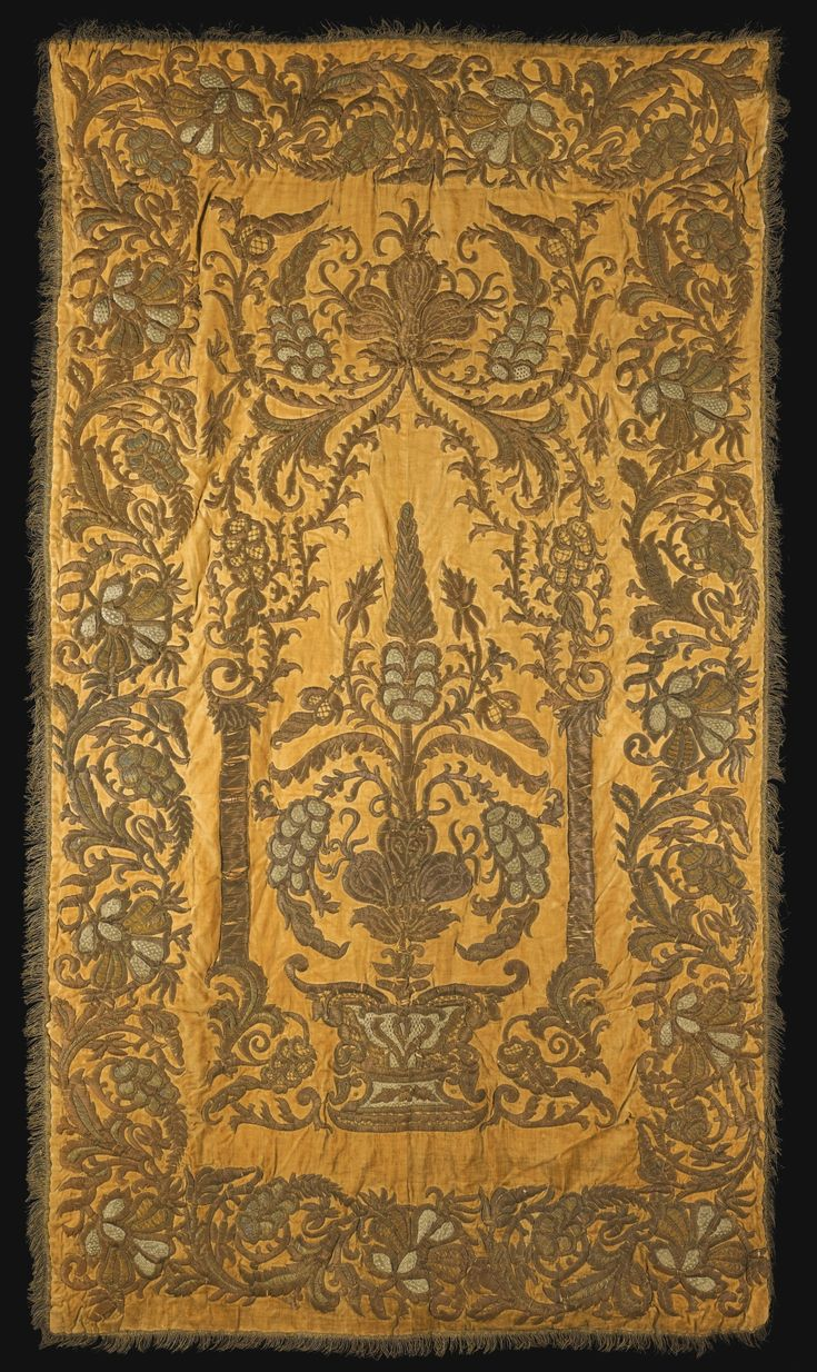 AN OTTOMAN SILK AND METAL-THREAD EMBROIDERED PANEL, 18TH CENTURY of rectangular form, decorated with appliqué work composed of silver, bronze and gold coloured threads on an ochre velvet ground with a design centering on a foliate tree emanating from an ornate vase between two columns under a vegetal canopy, the border with scrolling floral vines