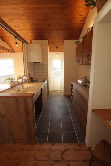 キッチンの足場板がアクセントのゆったり暮らせるフラットハウス