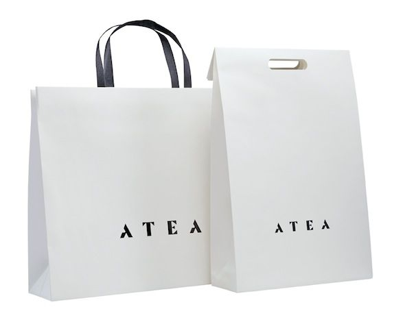 Luxury retail bags & mailing cartons for Atea. Off white Kraft paper with black foil blocking and paper twist handles.