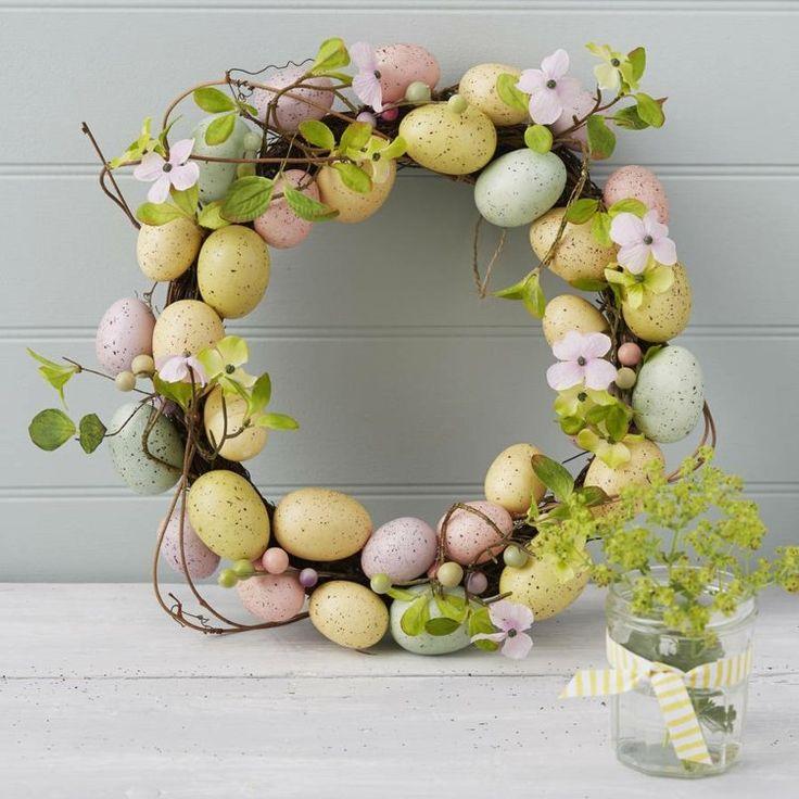 décoration de porte d'entrée pour Pâques - une couronne de porte en branches fleuries et œufs aux couleurs pastel