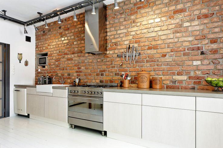 L-formet køkken med lille ø til spiseplads. De rå murstensvægge giver en fantastisk fin dekoration i boligindretningen.