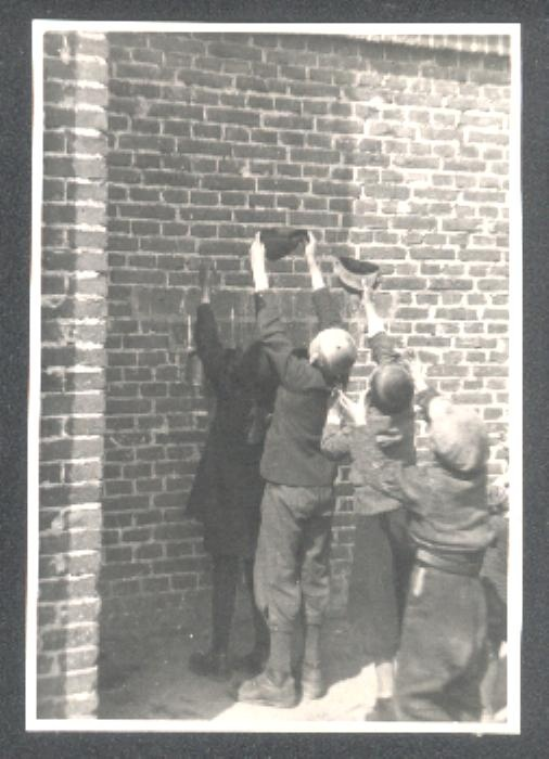 Jewish children inside the Warsaw Ghetto hold up their hats for bits of food tossed over the wall by kind, and brave, passers-by.  Anyone, Pole, Jew, or German, could face summary execution if caught throwing food into the Ghetto.