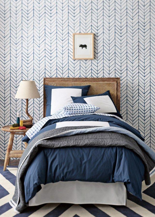 Un peu trop de bleu et de motifs dans cette chambre d'ado malgré de beaux éléments comme le papier-peint chevron, le tapis graphique, le linge et la tête de lit en bois #deco #chambre #bleu