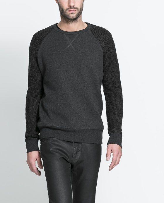 El hombre lleva un suéter negro. Esto suéter es muy bonito y quiero esto suéter. Esto suéter es informal, y formal. Puedes ir a un restaurante o una fiesta. Esto suéter no cuesta tanto, y es muy fantastico.