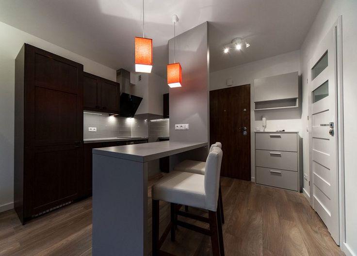 Modern, funkcionálisan berendezett kis 34 négyzetméteres lakás egy férfi részére. Az alapterület ugyan kicsi, de a látványelemeket nem nélkülözi teljesen a lakás, a nappali zónát szürke fal és gipszkarton álmennyezet definiálja süllyesztett világítással, a hálószobában az ágy mögötti fal megvilágított tégla textúrája ad remek hangulati elemet, a fürdőszobában pedig a narancssárga mozaik betét és a megvilágított beugró fali polcok vonzzák a szemet.