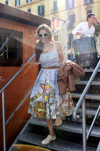 Kelly brook wearing beautiful 1950s-style cotton dress, shades & Superga plimsolls, while boyfriend Thom carries the suitcase - a proper contemporary starlet!