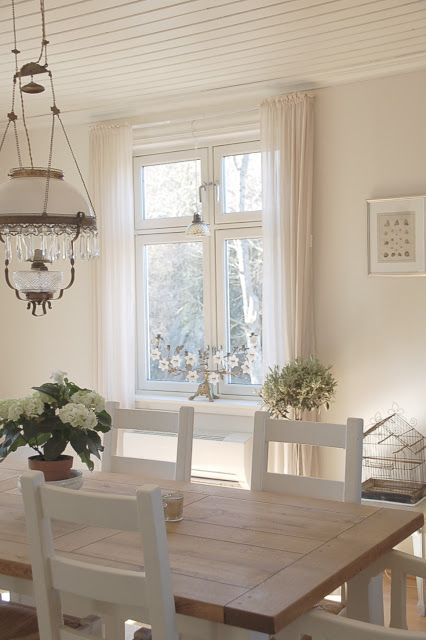 mesa comedor en noble madera con sillas blancas y araa deu