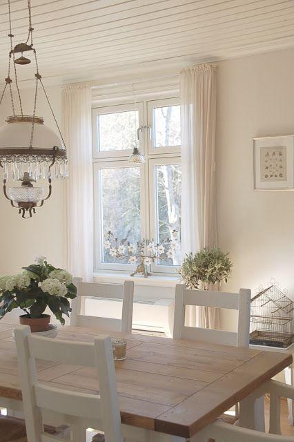 Delicado espacio.Mesa comedor en noble madera con sillas blancas y araña de…