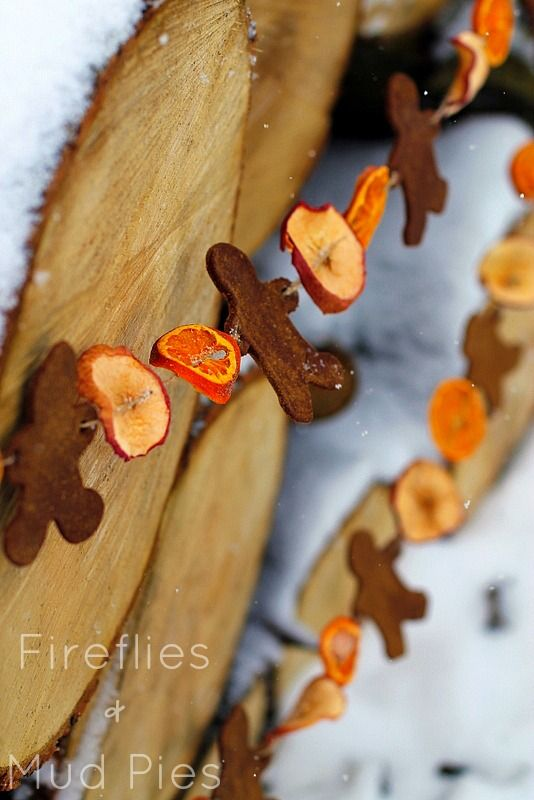 Invite your children to join in on making this fun, vintage holiday garland! First, bake thin slices of fruit in the oven. For the gingerbread men, mix cinnamon, cloves, and applesauce into a pliable clay. Once everything has dried, string the pieces on a strand of twine. Get the tutorial at Fireflies + Mud Pies. - CountryLiving.com
