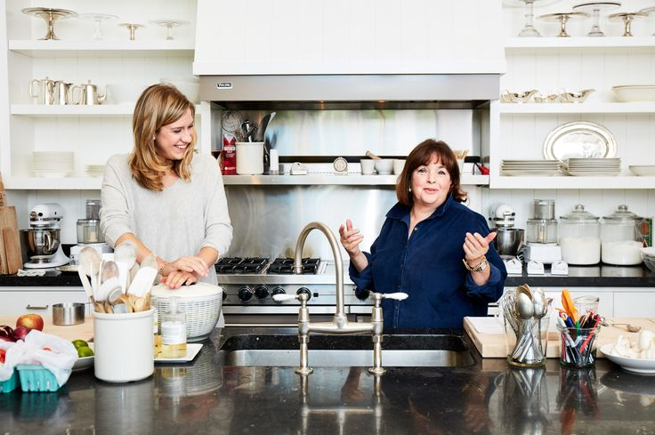 **** Ina Garten's working kitchen ... white cabinets & open shelves (beadboard backs), square tile backsplash, dark counters, wood floors, shelf over stainless stove, large deep sink with high spout