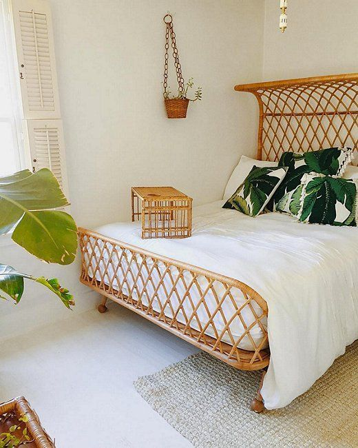 Love the pairing of the wicker bed frame and accessories with the crisp white bed linens and tropical print pillows!
