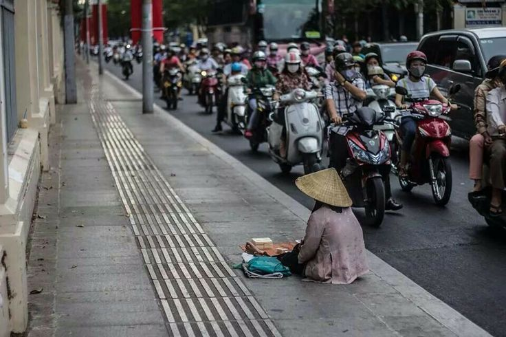 An elderly woman spends her days attempting to make a living as the world passes her by barely noticing her existence.  Photography in Ho Chi Minh City.