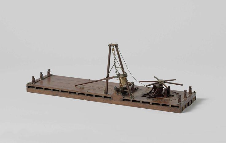 Anonymous | Model van een baggervlot, Anonymous, c. 1800 | Model van een baggervlot met baggerbeugel-installatie. De beugel met lange steel wordt met een lier bediend; het takel loopt door een blok aan een tweepootbok. Onder de bok een kraanbalk, die vermoedelijk als hefboomsteun dient. De kaapstander op het voordek werd voor de voortbeweging van het vlot met het anker gebruikt; drie meerpalen aan ieder eind en ringen op het dek langs de lange zijden.