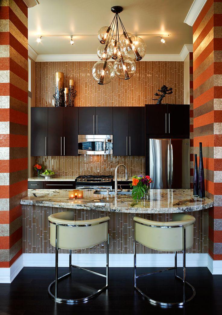 Люстра с прозрачными плафончиками, изогнутые лаковые спинки кресел и полосатые стены - создали гармоничный ансамбль  в интерьере кухни.