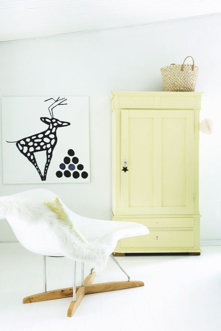A wonderful bright corner, with the classic designer chair from Eames combined with a vintage soft yellow closet.