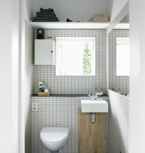 A tiled unit, topped with a long shelf for toiletries, houses the pipes and the tank for the wall-mounted toilet; a shelf mounted above the unit holds towels and other items