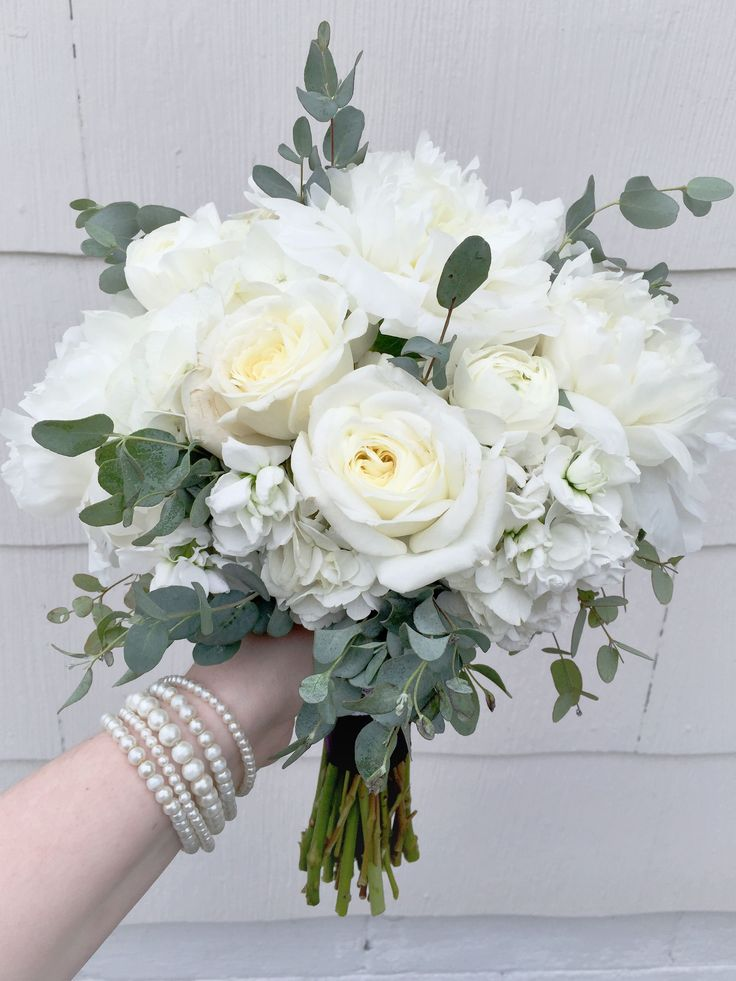 Elegant white bridesmaid's bouquet composed of peonies, stock, garden roses, ranunculus, and eucalyptus. Designed at West View Florist in Elkhart, IN 46514.