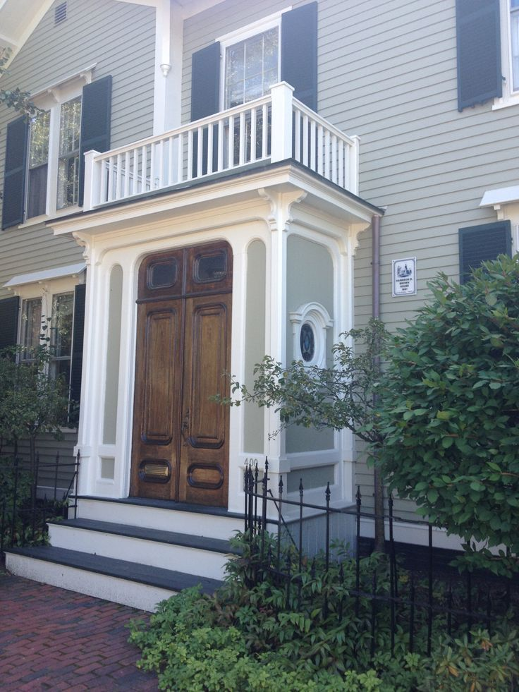 Classic enclosed small front porch with top railing and beautiful wood  double doors