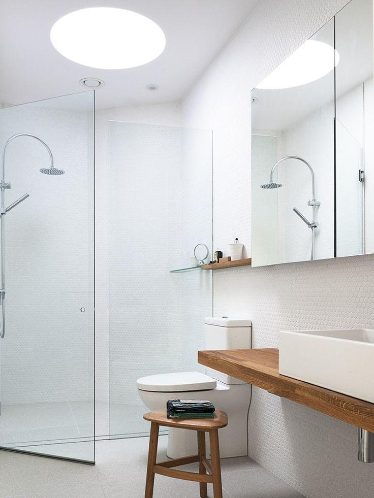 banheiro com pastilhas brancas e bancada de madeira