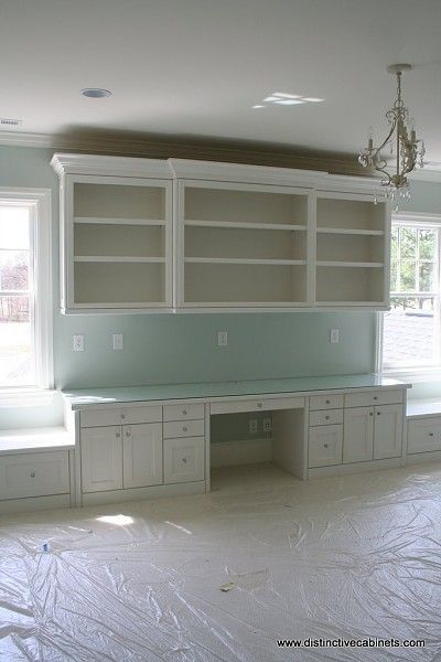 Built-in white desk area with open shelves above