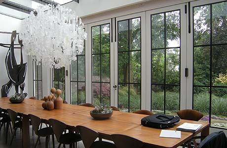Bi-folding doors with bronze casement inserts allow the room to open fully into the garden.