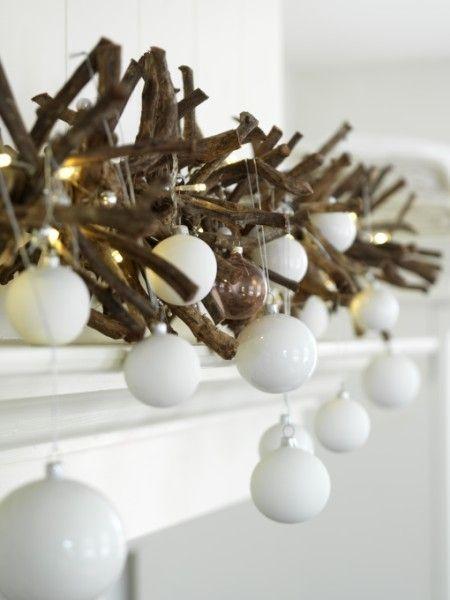 Espumillón de ramas secas con bolas blancas de cristal, como guirnalda para la chimenea.